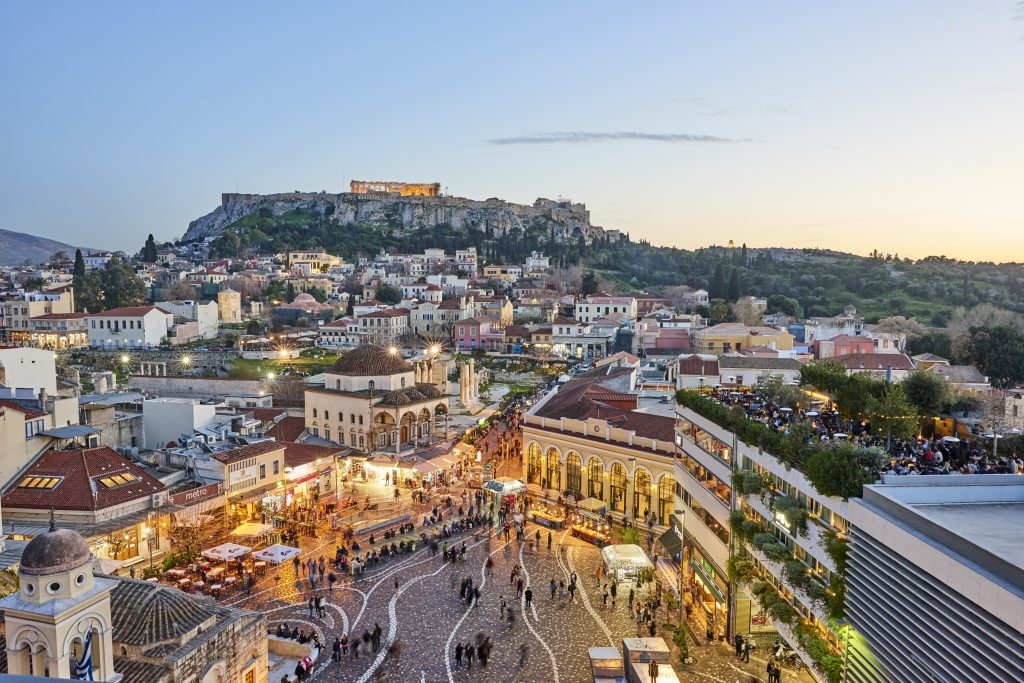 Athens, Greece - February 13, 2016: Aerial view of Athens at sunset with an illuminated Acropolis in the background. In foreground tourists and local people in Monastiraki Square. The clustered homes on the hill is known as Plaka.